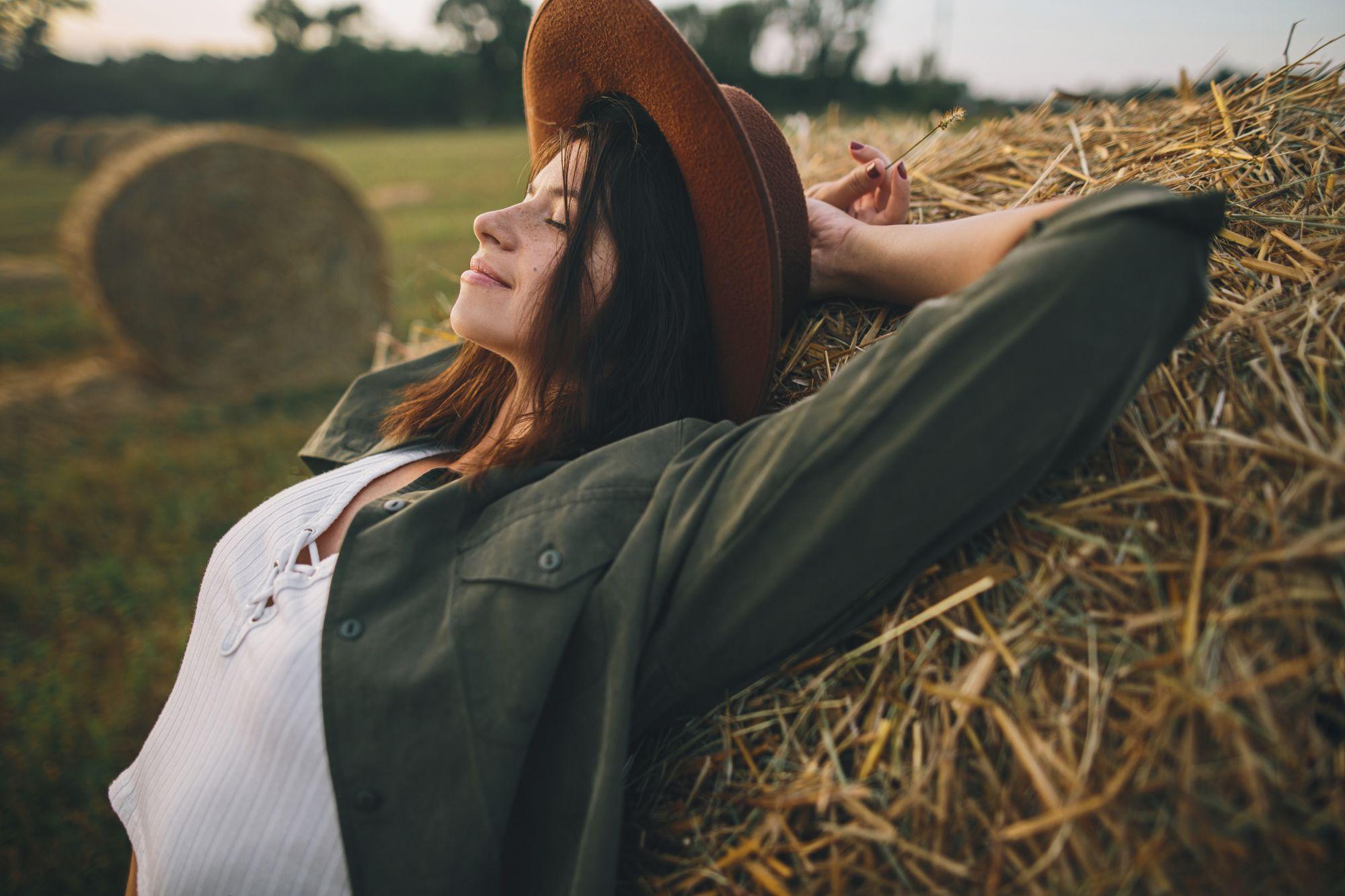 Nuori nainen hengittää rauhallisesti peltomaisemassa