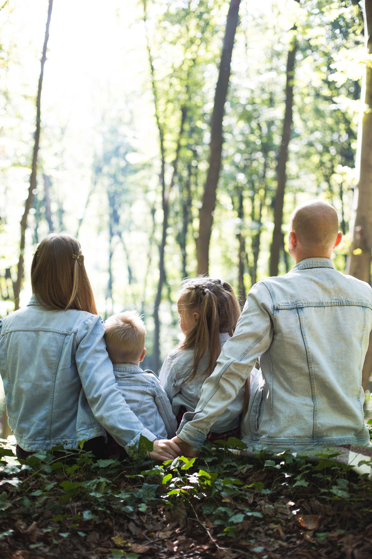 Perhe istumassa metsässä ja hengittämässä yhteistä ilmaa