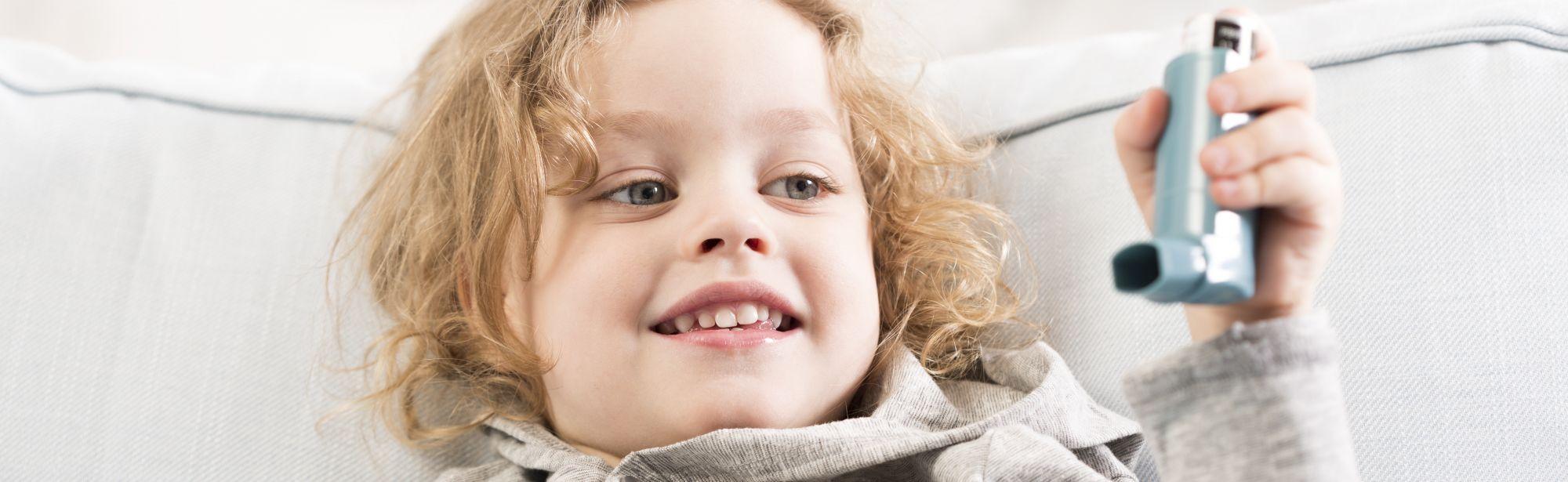 Nauravainen poikalapsi pitää inhalaattoria kädessä ja voi hyvin