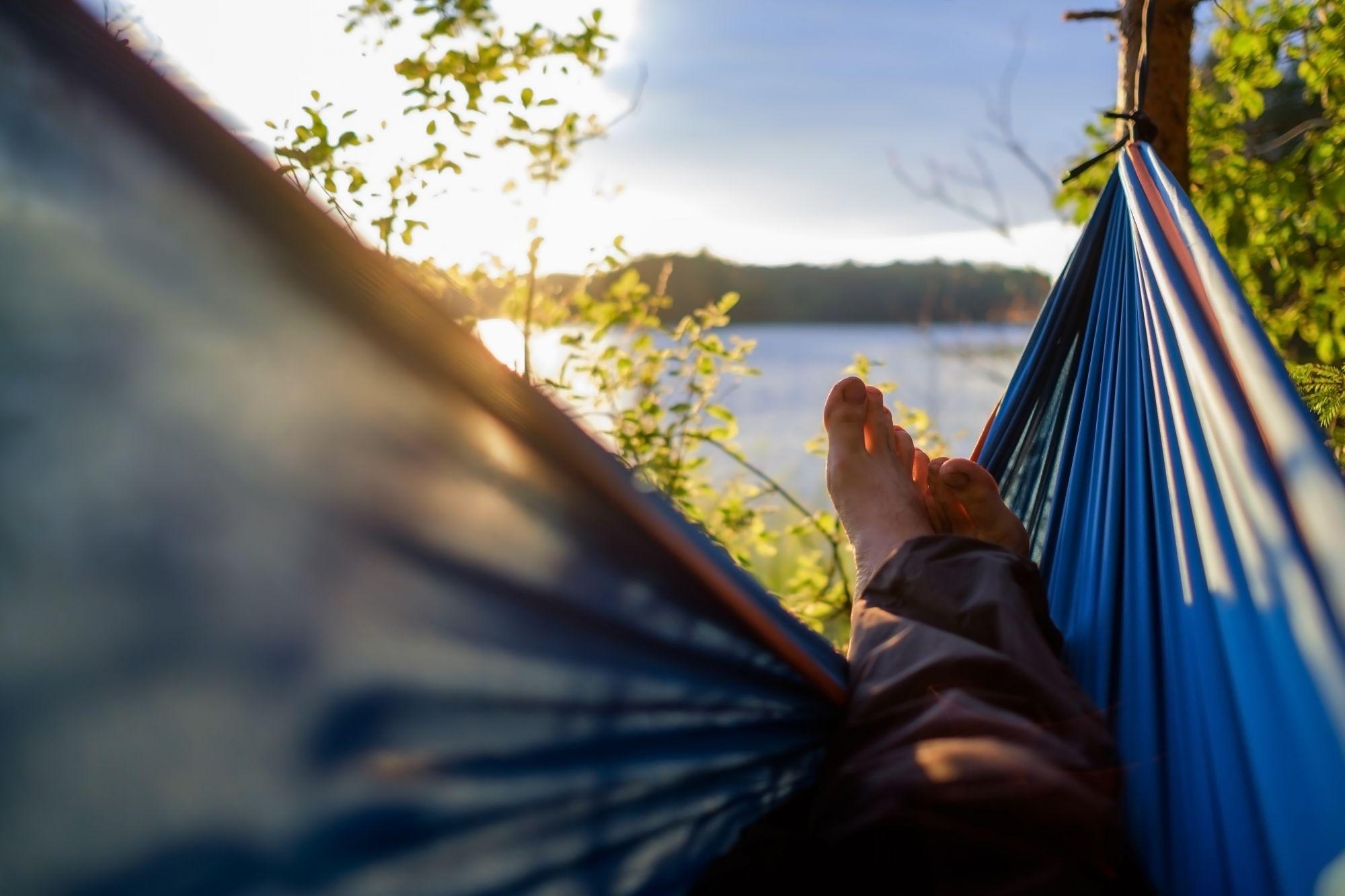 Mies rentoutuu lomalla riippukeinussa ilman työstressiä