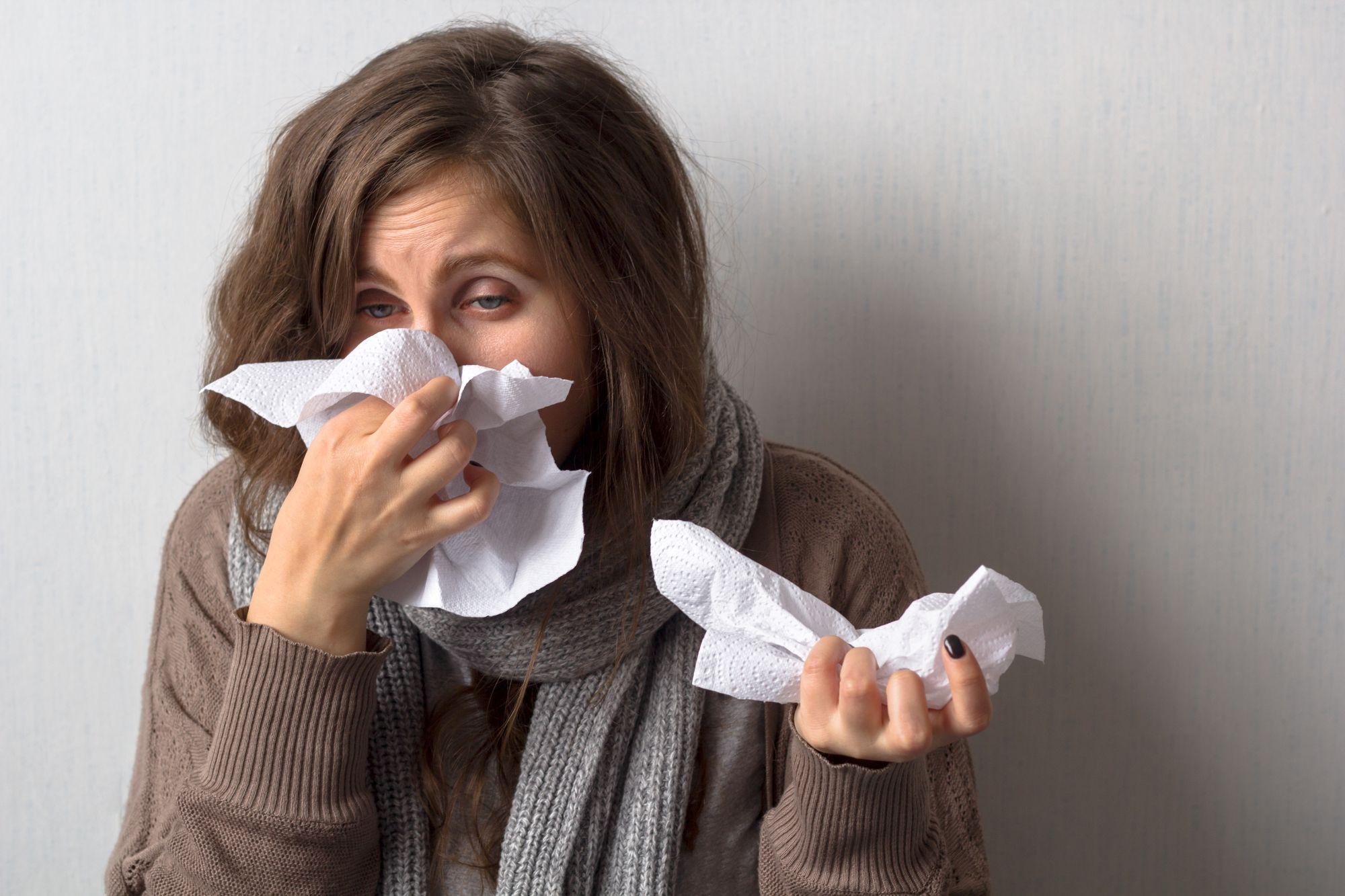 Nainen hengittää raskaasti flunssassa