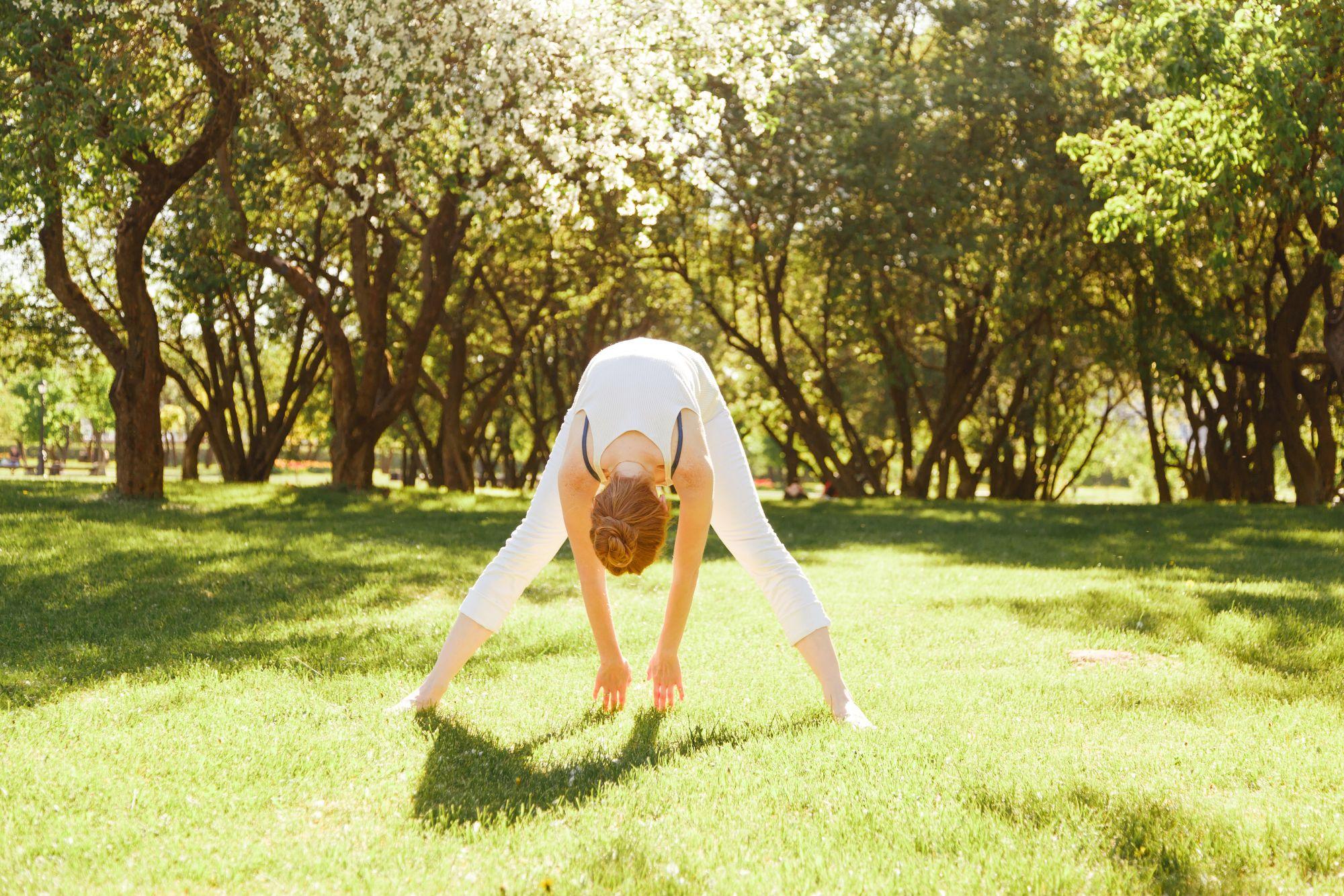 Nainen venyttelee puistossa ja näin parantaa hengitystään