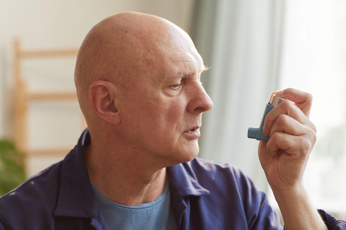 Mies ottaa inhaloitavaa lääkettä joka on yksi astman hoitokeinoista