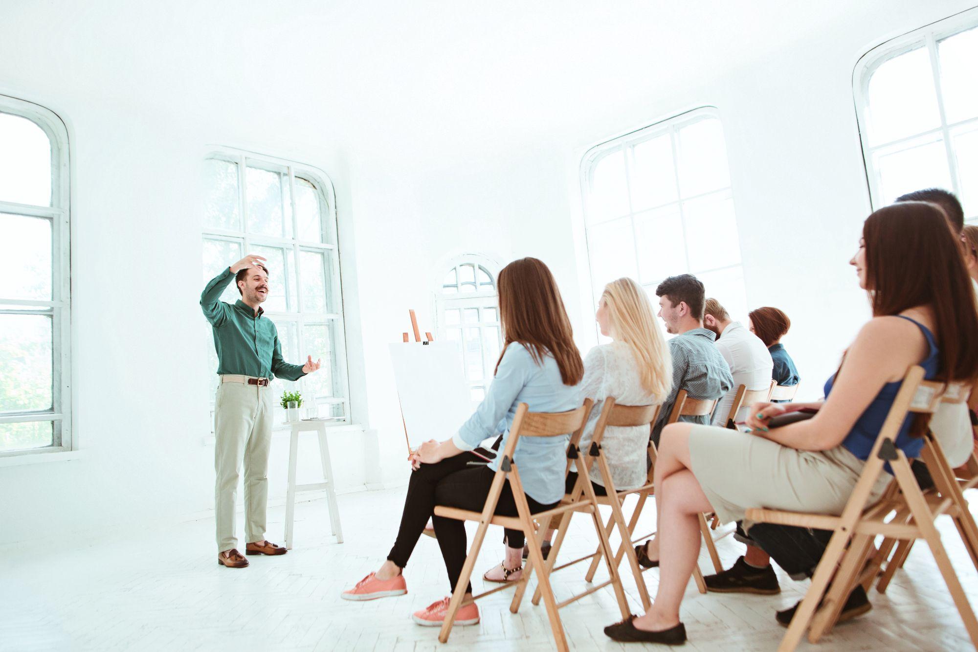Mies puhuu yleisölle eikä hengästy puhuessaan