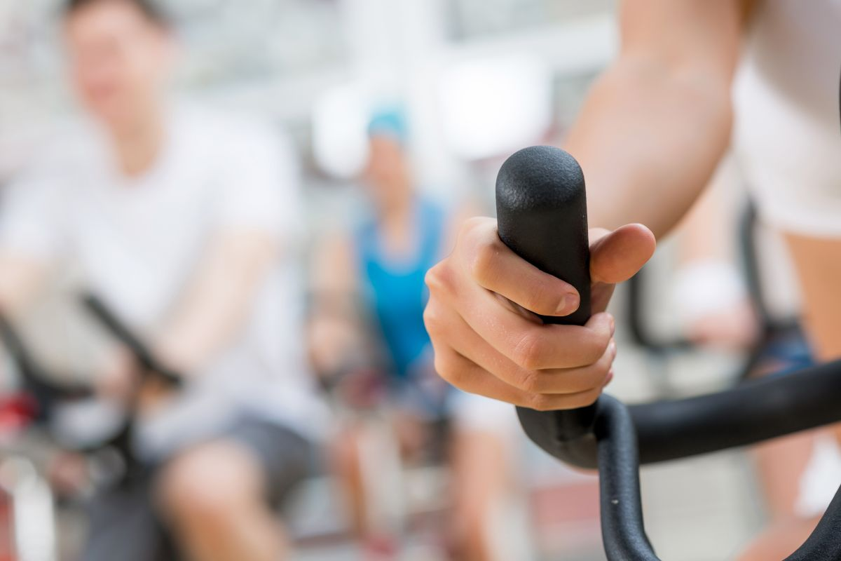 Nainen ryhmäliikuntatunnilla sisäpyöräilemässä