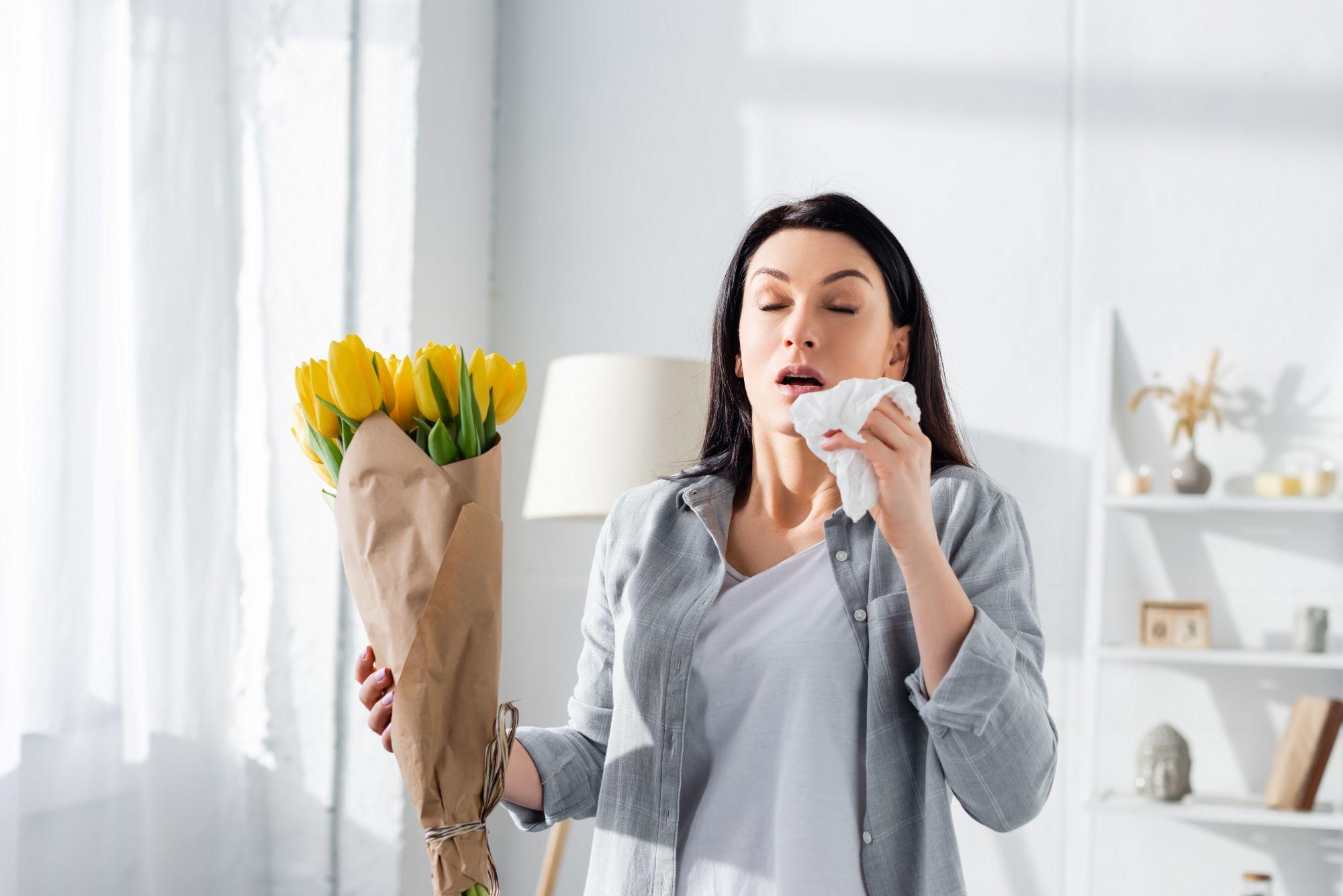 Nainen aivastaa kukkien tuoksusta