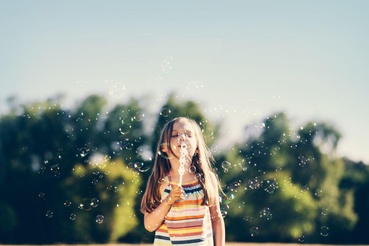 Pieni tyttö puhaltaa saippuakuplia