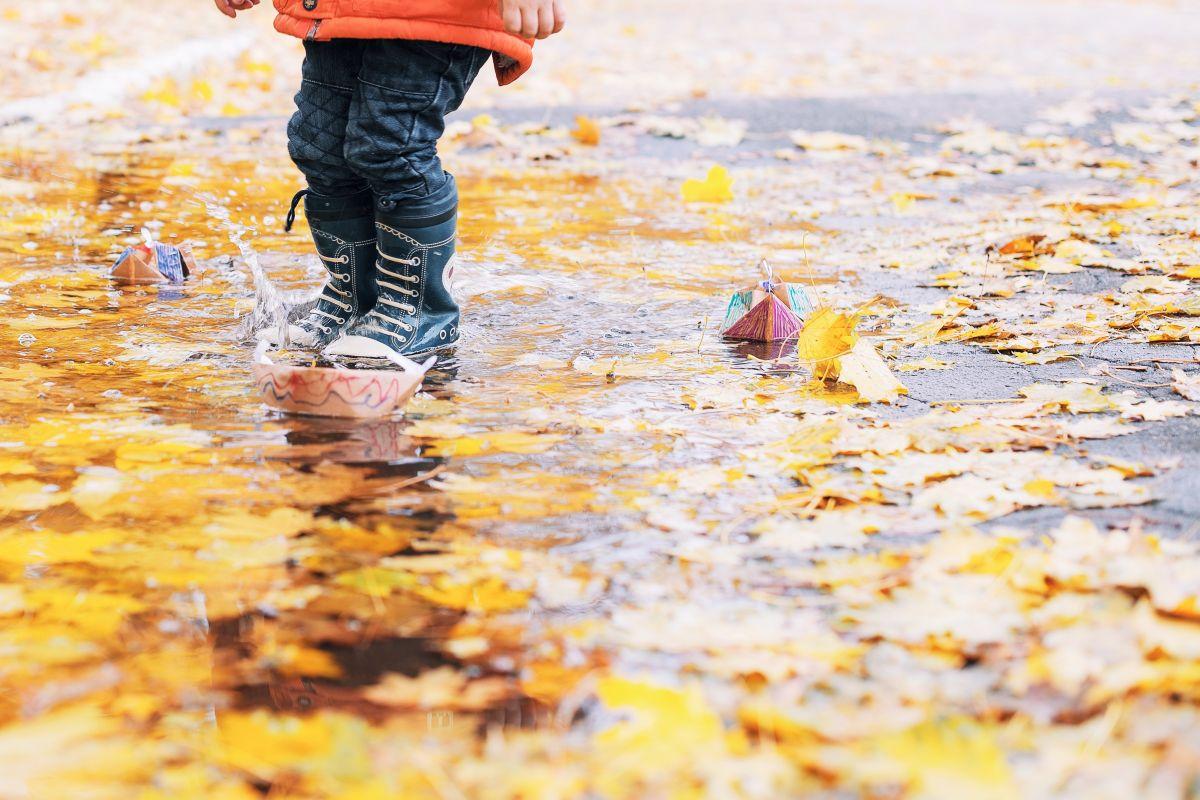 Lapsi leikkii syksyllä vesilammikossa