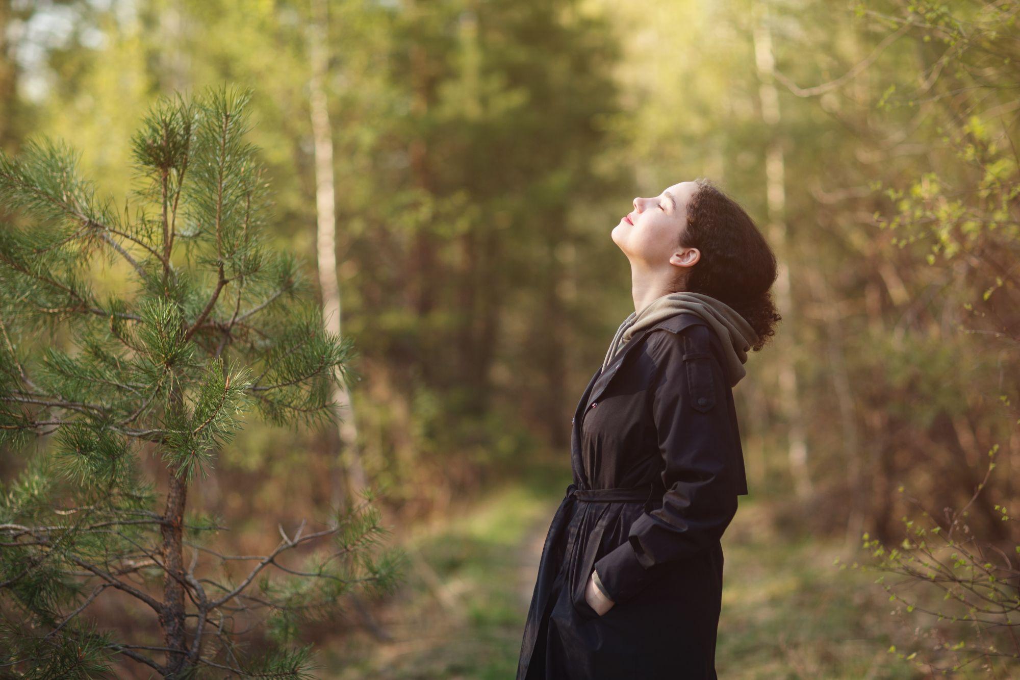 Nainen tekee syvähengityksiä metsässä ja rauhoittaa mieltään